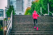 Runner running up the stairs on rain run in Vancouver city. Staircase cardio workout jogger training. poster