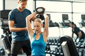 Trainer helping athletic woman at gym. Personal trainer giving weightlifting training to girl in gym. Young woman working out at gym using dumbbells with help of personal trainer. poster