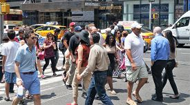 NEW YORK, NEW YORK - July 2, 2014: New York City Street Scene. Everyday people crossing a busy intersection in New York City. Some are texting and checking their phones.