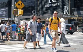 NEW YORK, NEW YORK - July 2, 2014: New York City Street Scene. Tourists and everyday people crossing a busy intersection in New York City.