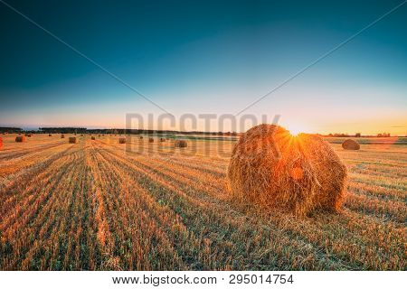 Rural Landscape Field Meadow With Hay Bales During Sunny Evening In Late Summer. Hay Stacks In Sunli
