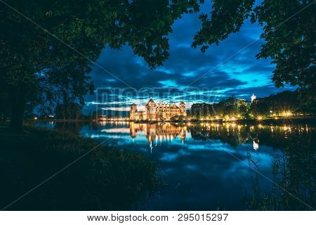 Mir, Belarus. Night Scenic View Of Mir Castle In Evening Illumination With Glow Reflections On Lake