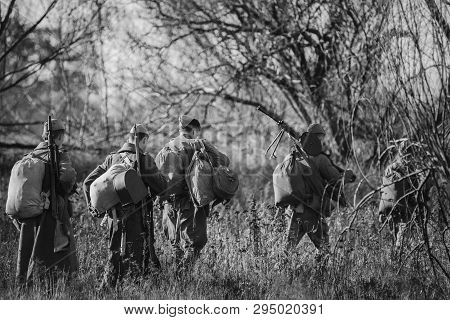 Re-enactors Dressed As World War Ii Russian Soviet Red Army Soldiers Marching Through Forest. Photo