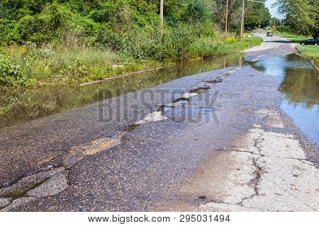 Damaged road full of potholes and puddles after a rainstorm