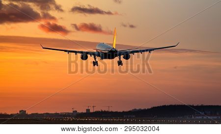 Plane Is Landing At Airport During A Wonderful Orange Sunset Sky / Silhouette Of Airplane In  Dramat