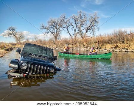 Brighton, CO, USA - April 6, 2019 : Women in a canoe are passing Jeep Wrangler stuck deep in the river, early spring scenery on the South Platte River.