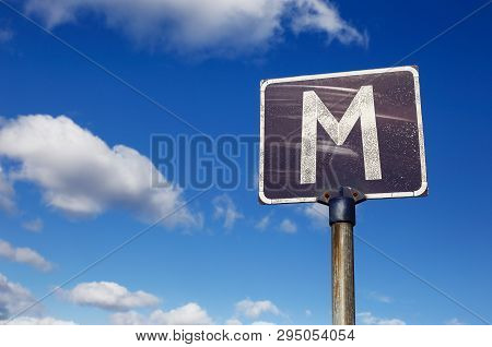 One Weathered Road Sign With Letter M Indicate A Meeting Point On A Narrow Road Against A Blue Cloud