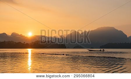 Silhouette Image Of A  Boat Sailing In A Dam In Southern Of Thailand In The Morning.