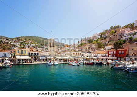 Hydra, Greece - June 2, 2018: Beautiful Harbor With Cycladic Architecture Hillside Town Behind, On T