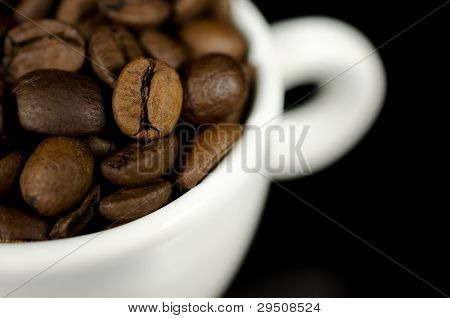 Close Up Photograph Of Brown Coffee Beans In A White Mug.