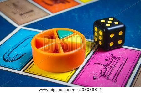 London, Uk - 07 April 2019: Close-up Of Classic Board Game Trivial Pursuit With Black Die And Colore