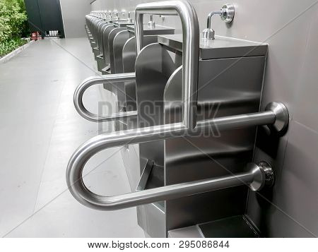 Closeup Men Urinal For Cripple Person In Public Toilet. Designed And Made From Stainless Steel To Pr