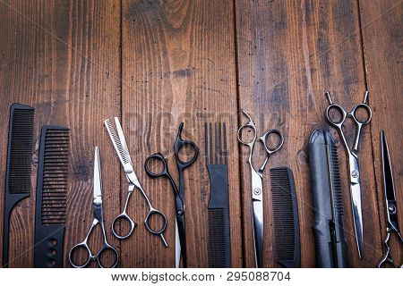 Stylish professional barber scissors combs on vintage wooden table, hairdresser salon concept, hairdressing tool set. Haircut accessories