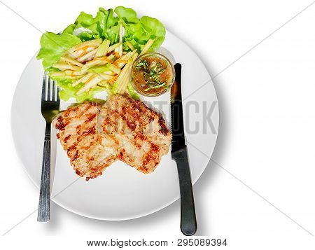 Top view fusion pork steak in Laos style with green apple on white plate and background. Steak Laos is a steak that combines Laos by tamarind sauce mixed rice crush with green apple as a side dish. poster