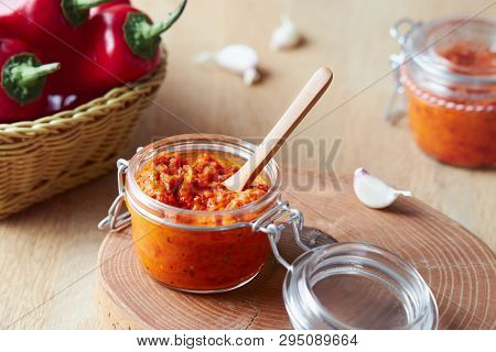Roasted red pepper relish (Ajvar) in a jar with ingredients