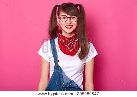 Portrait of cheerful beautiful girl with long pigtails, wears t shirt, denim overalls and red bandana on neck. Attractive schoolgirl with toothy smile poses in studio isolated over pink background. poster