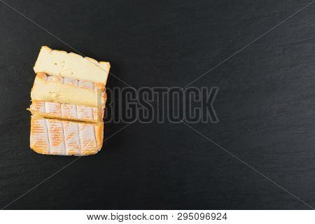 Cheeseboard With Sliced Yellow Limburger Cheese Top View