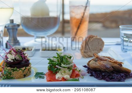 Restaurant Table With Served Entree Plate With Small Snacks. Al Fresco Fine Dining Settings With Wat