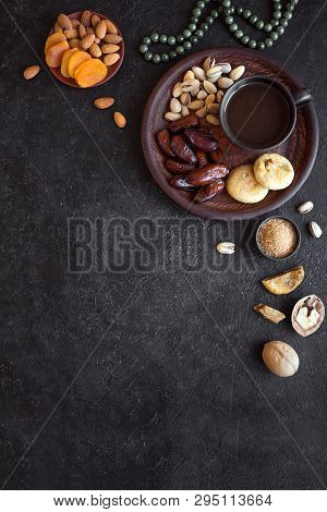 Traditional Muslim Iftar Food On Black, Copy Space. Ramadan Kareem With Dates, Nuts, Dried Fruits An