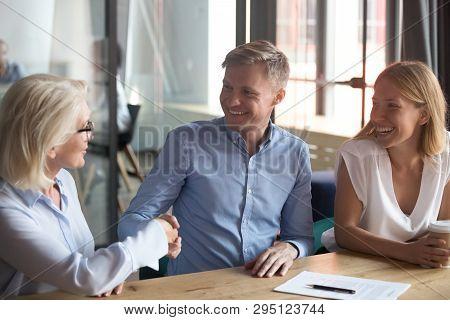 Old Female Broker Handshake Happy Young Couple Clients Make Deal