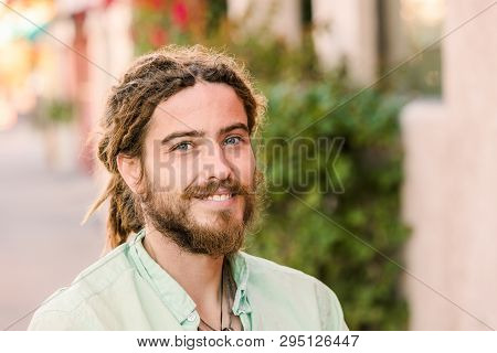 Handsome Young Man With Beard Smiling Outdoors