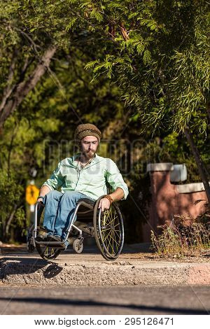 Young Man In Wheelchair Negotiates High City Curb