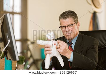 Angry Professional Man Putting A Pin Into The Heart Of A Voodoo Doll