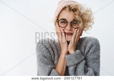 Portrait of excited and cute enthusiastic good-looking girlfriend feeling upbeat and thrilled before holiday trip smiling holding palms on cheeks wearing pink beanie and sweater over white wall poster