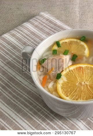Delicious Chicken Soup With Lemon, Rise, Carrot And Green Onion. Top View. Striped Serviette. Rustic