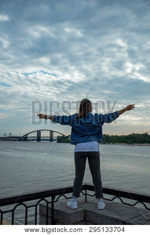 Woman Looking On Sunrise Over The River. Hands Rise Up