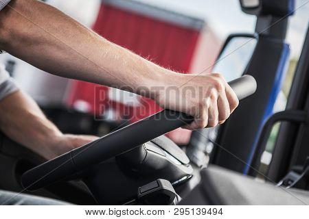 Hand On Truck Steering Wheel. Caucasian Trucker On The Road. Closeup Photo. Transportation Industry.