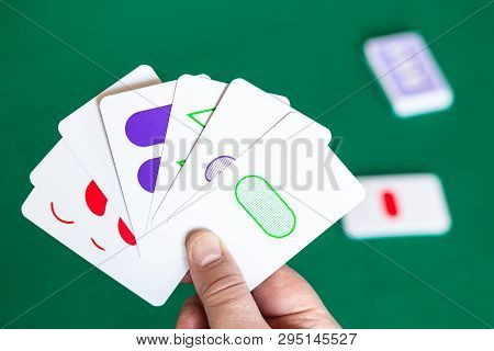 Moscow, Russia - April 3, 2019: Player Shows Set Game Cards Over Green Table. Set Is Real-time Card