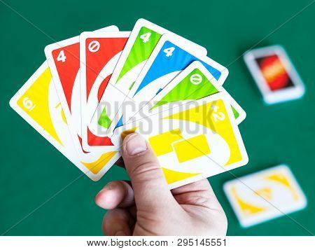 Moscow, Russia - April 3, 2019: Player Shoes Uno Game Cards Over Green Table. Uno Is Shedding-type C