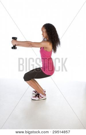 Young biracial dark skinned female of Chinese, African-American, German and Middle Eastern origin in red tank top and black sporty pants fitness exercise work out with dumbbell