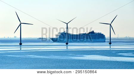 A Large Cruise Ship Passes Offshore Wind Turbines Near The Oresund Bridge Between Denmark And Sweden