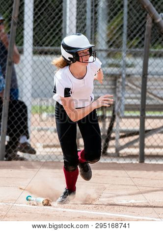 Red Haired High School Softball Player Hustling Up The First Base Line After Hitting The Ball.