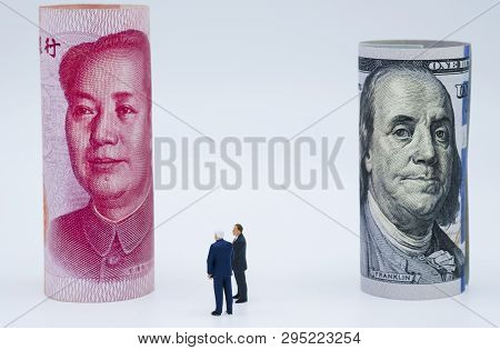 Miniature Business Men With Us Dollar And China Yuan Banknote On Cooperate Meeting For Trade War.cop