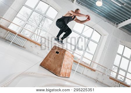 Strong Fitness Man Doing Jump Exercises On Box In Gym. Fit Athlete Wearing Sportswear And Jumping Ov