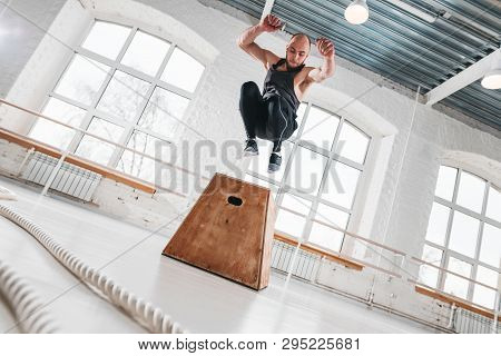 Dynamic Shot Of Fit Athlete Jumping Over Cross Box In Fitness Club. Strong Man Doing Jump Exercises