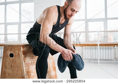 Sweaty Fit Man Sitting On Box And Hold Towel In Hand After Intense Cross Workout. Fitness Athlete Re