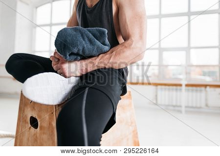 Muscular Tired Man Resting On Box And Hold Towel In Hand. Perspiring Fit Athlete Relaxing In Sport G