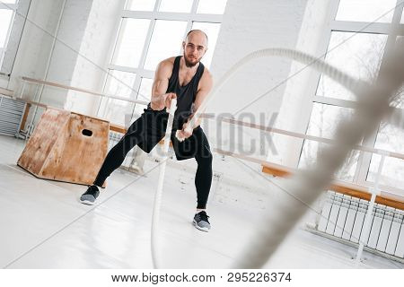 Dynamin Shot Of Strong Man Workout With Battle Ropes At Light Gym. Muscular Sportsman Doing Cross Ex
