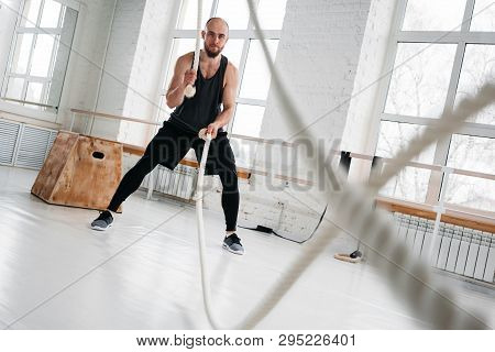 Dynamic Shot Of Strong Man Workout With Battle Ropes At Light Gym. Muscular Sportsman Doing Cross Ex
