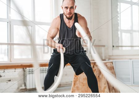 Strong Male Athlete Doing Exercises With Rope At Gym. Working Out With Battle Ropes At Cross Gym