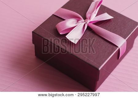 Purple Decorative Gift Box With Small Bow And Pink Ribbon On Pink Background