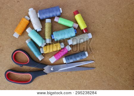 Multicolor Sewing Threads On A Roll For Sewing And Tailoring Scissors On A Wooden Background. With C