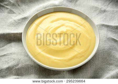 Bowl Of Vanilla Custard On Rustic Background