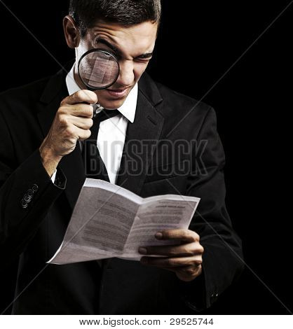 portrait of a handsome young man looking at a contract against a black background