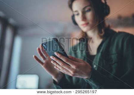 Young Handsome Girl Relaxing At Modern Home, Wearing Casual Clothes, Playing Music On Smartphone And
