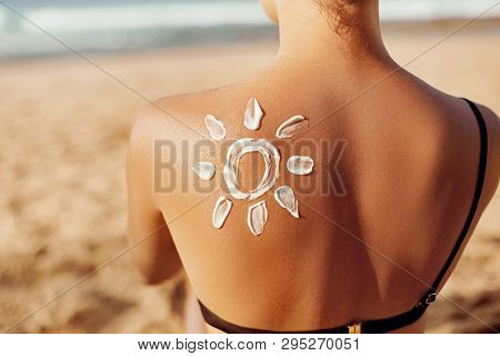 Skin Care. Sun Protection. Woman Apply Sun Cream. Woman With Suntan Lotion On Beach In Form Of The S